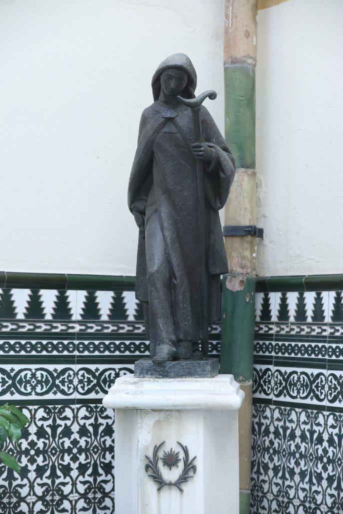 Una estatuilla de Santa Teresa sobre pedestal de piedra, situada en el patio de la Casa Hermandad, recuerda igualmente a la Patrona de tan egregios hermanos.